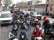 Many people riding motorcycles down street